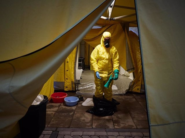 Un voluntario de DYA Navarra se desinfecta y se quita el traje EPI después de la jornada de limpieza y desinfección en el Hospital de Navarra durante la cuarta semana de confinamiento por el Estado de Alarma decretado por el Gobierno de España con motivo