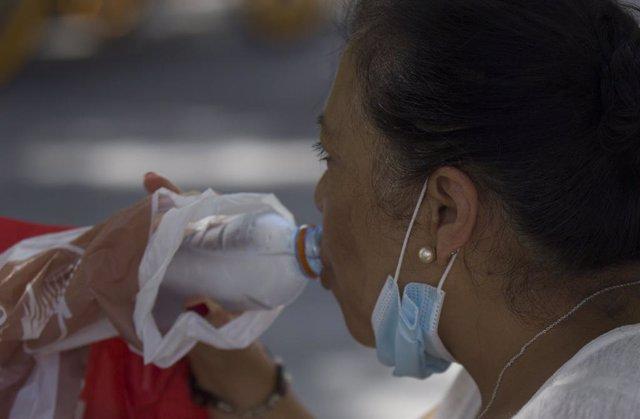 Una mujer bebiendo agua durante la ola de calor africano que ha llegado este jueves a España. En Sevilla (Andalucía, España), a 30 de julio de 2020.