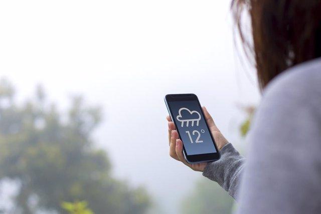 Mujer junto a una ventana mirando el pronóstico del tiempo en su móvil.