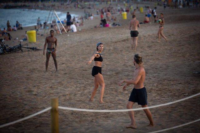Bañistas juegan en la playa en Barcelona, Catalunya (España), a 28 de julio de 2020.