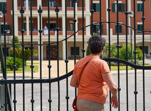 Una señora saluda desde la reja a un familiar en la residencia de ancianos de San Juan de Dios después de que la Junta de Andalucía permita visitar durante una hora a mayores en residencias. Sevilla a 02 de mayo del 2020