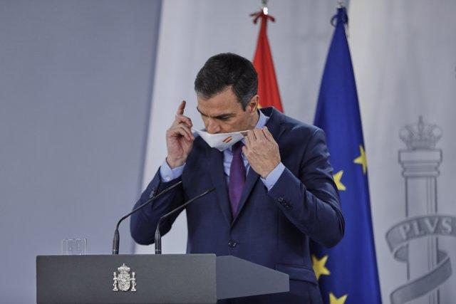 El presidente del Gobierno, Pedro Sánchez, se retira la mascarilla antes de ofrecer la última rueda de prensa posterior a la reunión del Consejo de Ministros y antes de las vacaciones, en Moncloa, en Madrid (España), a 4 de agosto de 2020