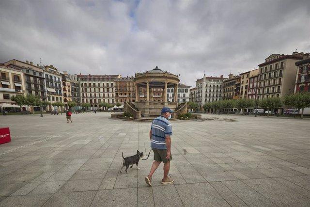 Un hombre con mascarilla pasea por la Plaza del Castillo de Pamplona