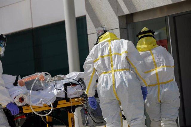 Varios sanitarios trasladan a un paciente desde el interior de la unidad móvil del SUMMA hasta la entrada del Hospital Puerta de Hierro tras haberle trasladado anteriormente desde la UVI del hospital temporal de IFEMA, durante un día de trabajo del Servic