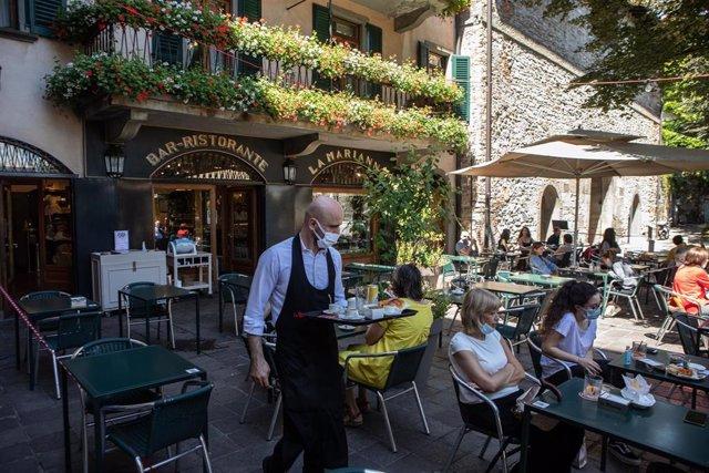 Un camarero con mascarilla sirve a unos clientes en una terraza de un restaurante en Bérgamo, Italia