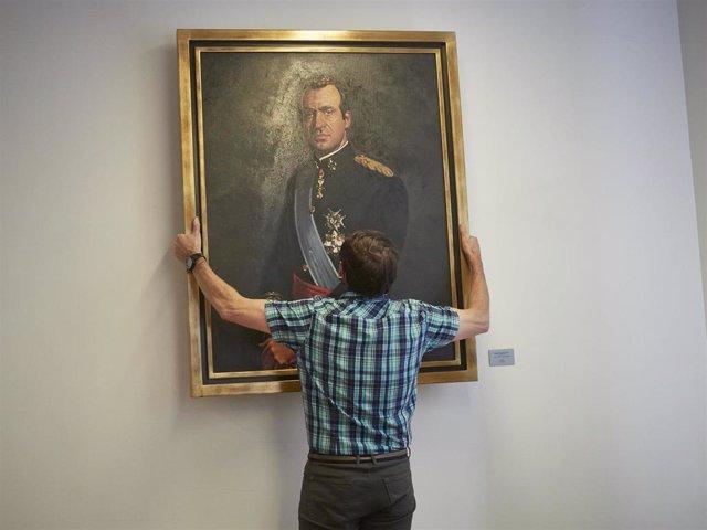 Un operario retira el retrato del rey emérito Juan Carlos I de la Sala de Gobierno del Legislativo foral del Parlamento de Navarra