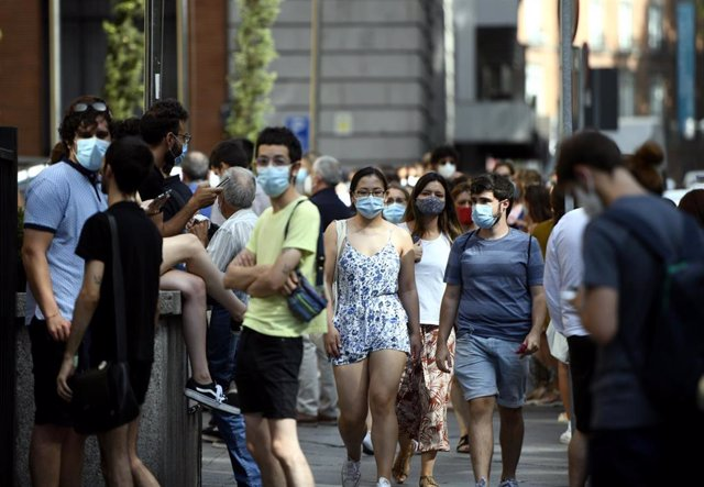 Varias personas caminan con mascarilla por una calle del centro de Madrid.