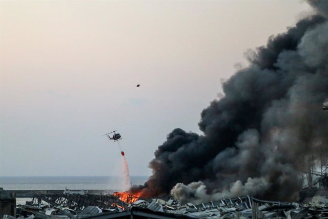 04 August 2020, Lebanon, Beirut: A military helicopter tries to put out a fire at the site of a massive explosion in Beirut's port. Photo: Marwan Naamani/dpa
