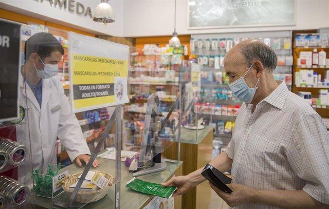 Un hombre adquiere las mascarillas gratuitas que el Gobierno andaluz empieza desde este miércoles 22, a través de las farmacias, a los ciudadanos mayores de 80 años. En Sevilla, (Andalucía, España), a 22 de julio de 2020.