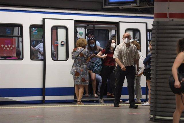 Pasajeros con mascarilla salen de un vagón en la estación de Metro de Atocha, en Madrid.
