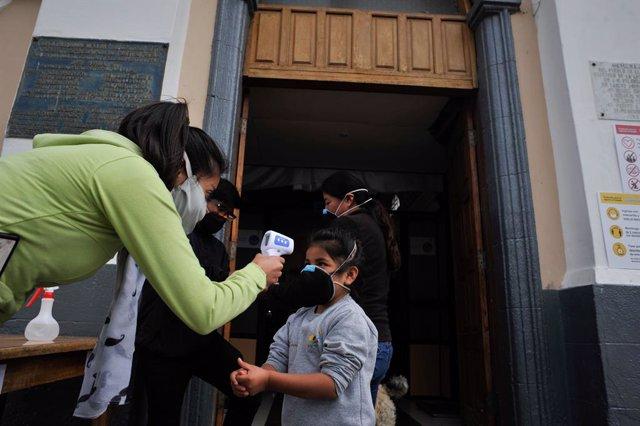 Una mujer le toma la temperatura a un niño en Quito durante la pandemia de coronavirus