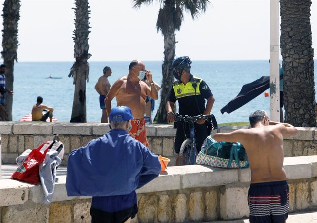 Policía Local informa a un bañista en la playa de La Malagueta. En Málaga (Andalucía, España), a 19 de julio de 2020.