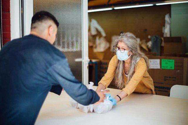Una voluntària del Banc dels Aliments de Barcelona, repartint menjar durant la crisi sanitària del Covid-19