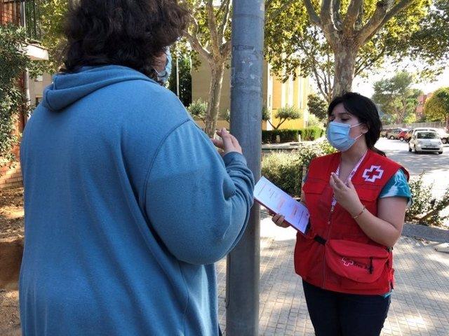 Una voluntària de Creu Vermella de Sabadell, informa a un vianant