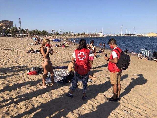 Dos joves voluntaris de Creu Vermella informen als seus parells de les mesures de prevenció contra el coronavirus, aquest divendres 7 d'agost del 2020 a la platja del Somorrostro de Barcelona.