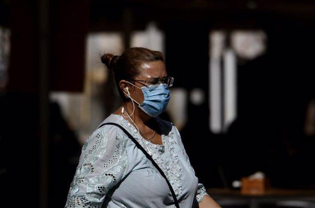 Una mujer camina con mascarilla, foto de archivo
