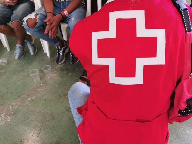 Un voluntario de Cruz Roja atiende a inmigrantes, foto de archivo