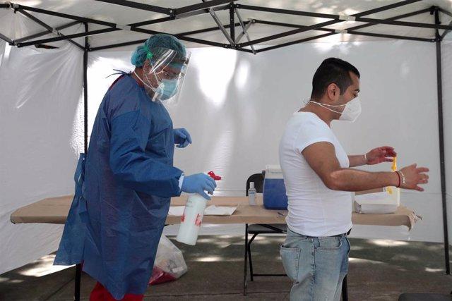 Un trabajador sanitario desinfecta a un hombre antes de someterle a la prueba de la COVID-19 en las instalaciones levantadas en el parque Salesiano de Ciudad de México.