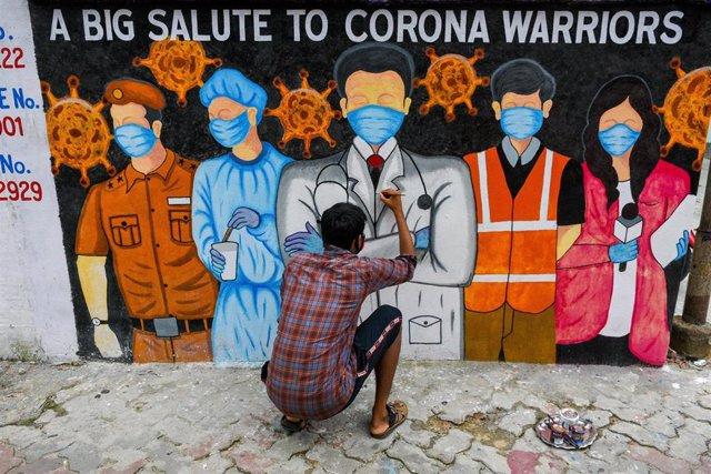 Un artista local de Calcuta da los últimos retoques a un mural en el que se agradece la labor de los trabajadores que se encuentran en primera línea luchando contra la pandemia en India.