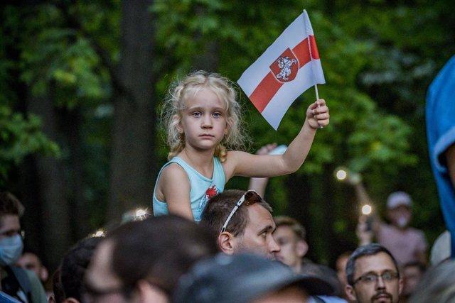 Una niña sostiene una vieja bandera de Bielorrusia, símbolo de protesta contra el Gobierno de Bielorrusa, durante el mitin de campaña de la candidata presidencial Svetlana Tikhanovskaya antes de las elecciones presidenciales.