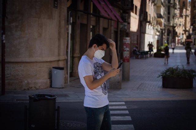 Un jove protegit amb mascarilla camina per un carrer del centre de Lleida, capital de la comarca del Segrià, a Lleida.