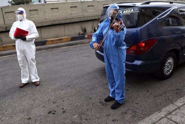 Un violinista y un sacerdote durante un acto religioso celebrado en las calles de de Bogotá por la muerte de una persona a causa de la COVID-19.