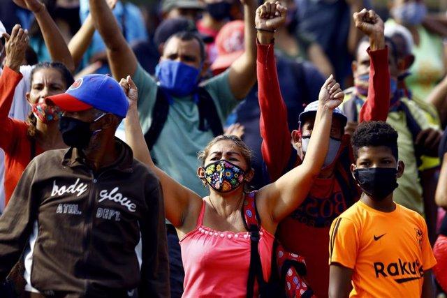 Trabajadores del mercado informal cercano a la Plaza de Toros Monumental de la ciudad venezolana de Valencia protestan por el cierre del las instlaciones por parte de las autoridades debid el aumento en el número de casos del nuevo coronavirus.