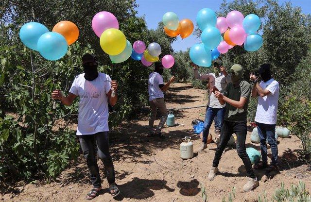 Palestinos se preparan para lanzar globos incendiarios desde Gaza a Israel.
