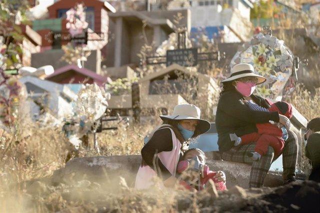 Dos mujeres esperan en un cementerio de la ciudad de Arequipa, en el sur de Perú, a que dé comienzo el servicio religioso por la muerte de un enfermo de coronavirus.