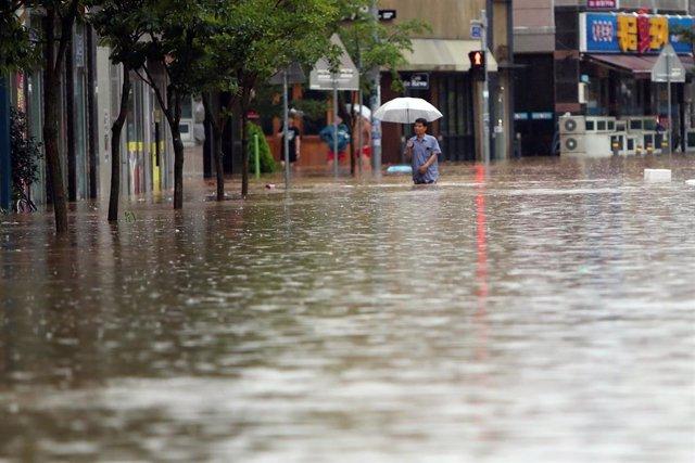 U hombre camina por una calle inundada en la ciudad de Gwangj, en el suroeste de Corea del Sur, en medio de las fuertes lluvias que han azotado la zona sur de la península.