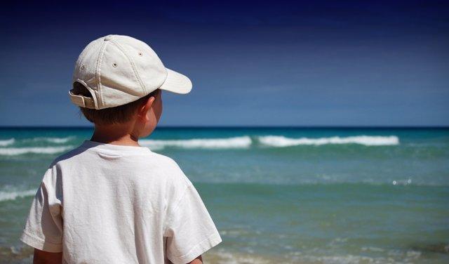 Niño con gorra en la playa.