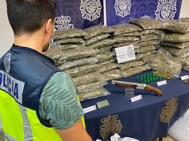 Un agente de la Policía Nacional junto a los efectos intervenidos en la operación First, con cuatro detenidos de una red que envasaba marihuana al vacío para venderla en el extranjero