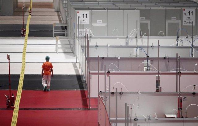 Una sanitaria camina por un pasillo entre mamparas de separación en el interior del hospital de campaña de IFEMA en el pabellón nueve durante su último día de funcionamiento por la bajada de la presión asistencial.