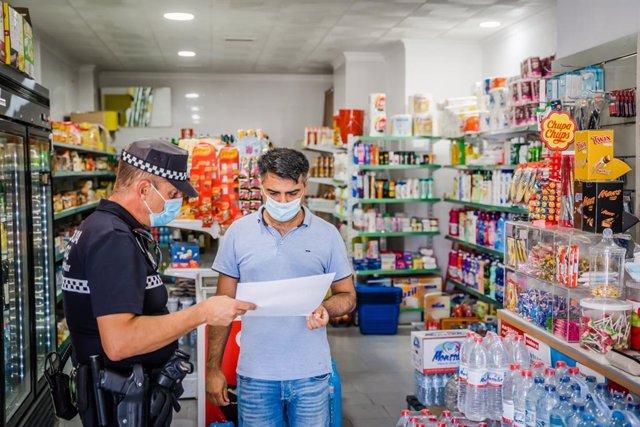 Un agente de la Policía Local reparte cartelería con información sobre la normativa anticovid-19