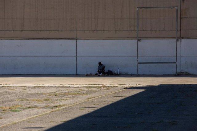 Un hombre descansa a la sombra junto al albergue de temporeros en Fira de Lleida, capital de la comarca del Segrià, en Lleida, Catalunya (España), a 6 de julio de 2020.