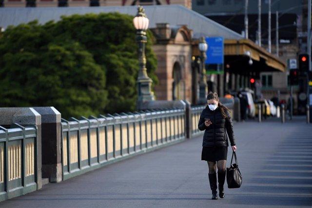 Una mujer transita una calle de Melbourne con una mascarilla puesta por el coronavirus.