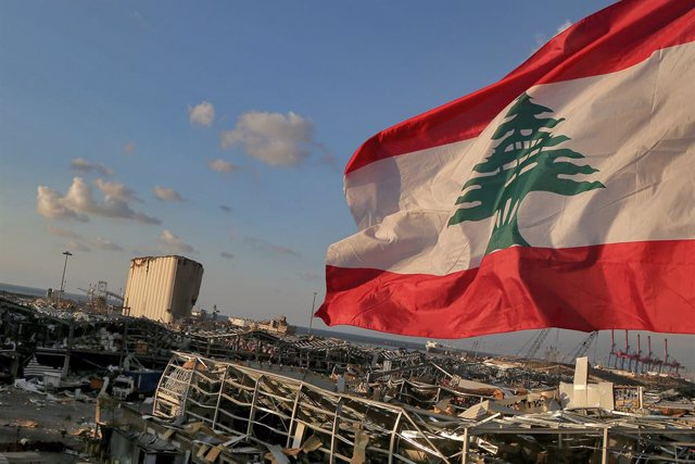 09 August 2020, Lebanon, Beirut: A Lebanese flag flies near the site where a massive explosion blasted the port of Beirut on the afternoon of 04 August which killed at least 158 people, wounded 6000 and displaced some 250,000 to 300,000.