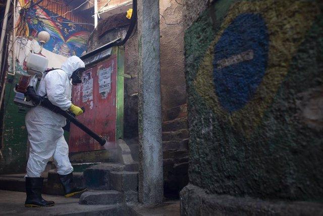 Un residente de la favela de Santa Marta, en el barrio carioca de Botafogo, en labores de de disinfección.