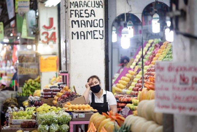 Una mujer en un puesto de frutas en un mercado en México