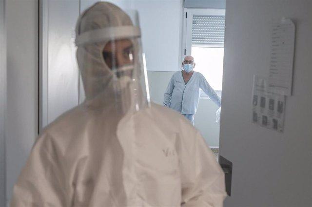 Trabajadores sanitarios entran en la habitación de un paciente negativo de Covid-19 en el Hospital Arnau de Vilanova, en Valencia, Comunidad Valenciana, (España), a 24 de abril de 2020.