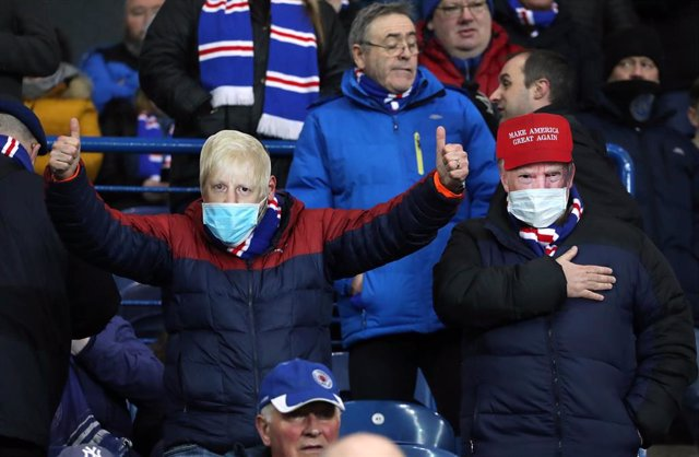 12 March 2020,Glasgow: Fan wearing the facemasks of UK Prime Minister Boris Johnson and US President Donald Trump in the stands during the UEFA Europa League round of 16 first leg soccer match between Rangers and Bayer Leverkusen at Ibrox Stadium.