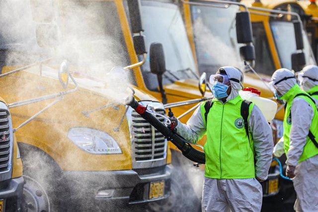 Imagen de archivo de trabajadores desinfectando camiones.