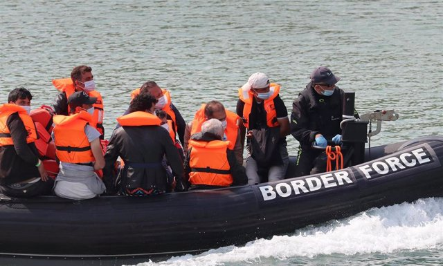 11 August 2020, England, Dover: A group of people thought to be migrants are brought into Dover by Border Force officers following a number of small boat incidents in the English Channel. Photo: Gareth Fuller/PA Wire/dpa