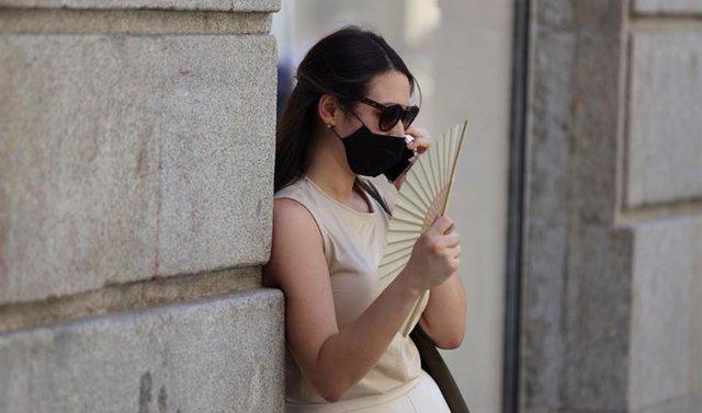 Una mujer con mascarilla y abanico