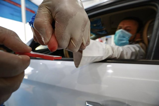 09 August 2020, Iraq, Najaf: An Iraqi medic collects drops of blood from a car driver on a blood collection test kit at a coronavirus (COVID-19) drive-through testing station. Photo: Ameer Al Mohammedaw/dpa
