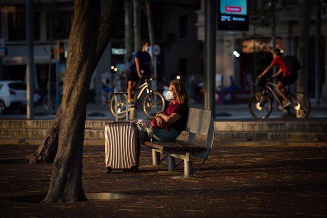 Una dona asseguda en un banc al costat d'una maleta, mentre diversos ciclistes passen per darrere, a Barcelona, Catalunya (Espanya), a 28 de juliol de 2020.