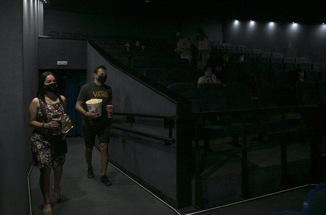 Una pareja entra en una sala de cine durante el primer fin de semana con estrenos en las pantallas