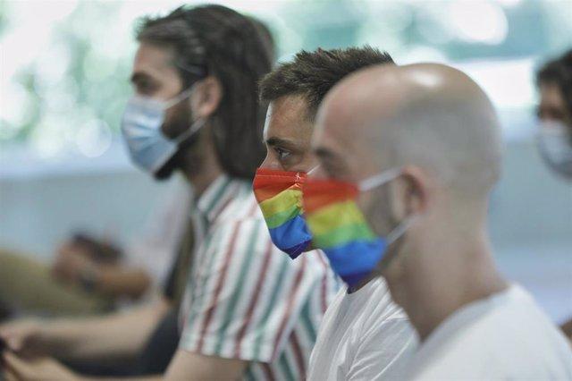 Dos hombres se protegen con mascarillas con la bandera LGTB durante su participación en el acto institucional con motivo del Orgullo 2020, en Madrid (España), a 29 de junio de 2020.