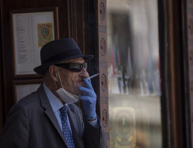 Un hombre con mascarilla y guantes fumando un cigarro durante el quinto día de la fase 2 en Sevilla a 29 de mayo de 2020