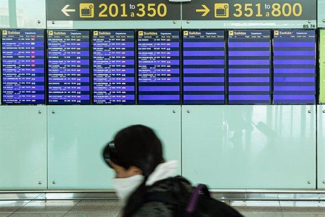 Una pasajera con mascarilla observa los paneles del aeropuerto El Prat de Barcelona durante el sexto día de confinamiento tras la declaración del estado de alarma por la pandemia de coronavirus, en Barcelona / Cataluña (España), a 20 de marzo de 2020.
